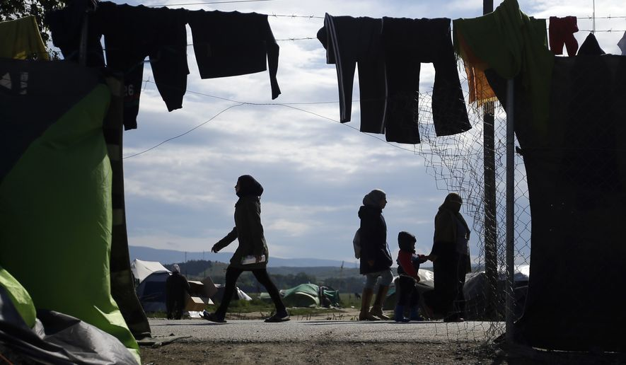 FILE- In this Thursday, May 5, 2016 file photo, migrants and refugees are silhouetted as they stroll through a makeshift camp at the northern Greek border point of Idomeni, Greece. A major aid agency says 27.8 million people around the world were internally displaced by conflict and natural disasters last year, or as many as the combined populations of New York City, London, Paris and Cairo. (AP Photo/Gregorio Borgia, File)