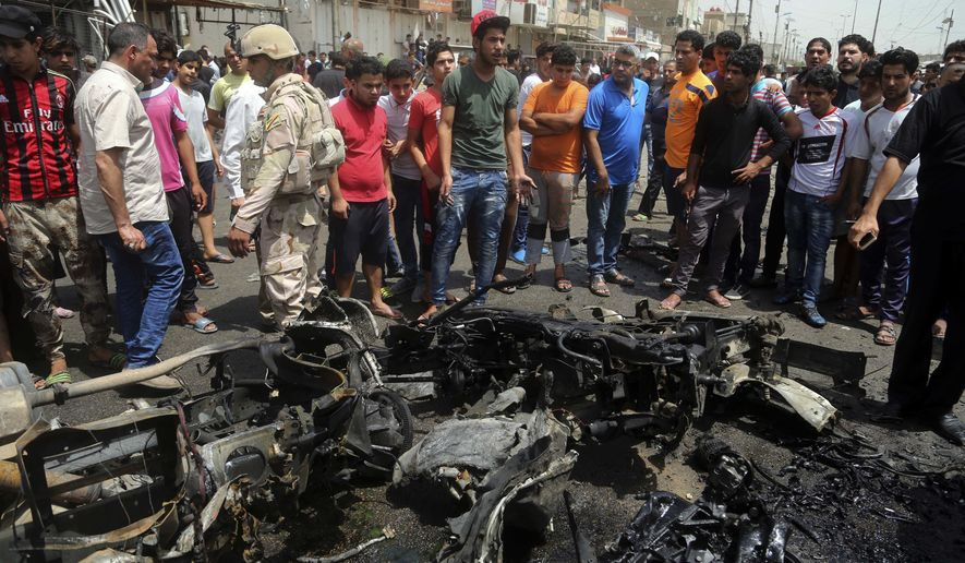 Security forces and citizens inspect the scene after a car bomb explosion at a crowded outdoor market in the Iraqi capital's eastern district of Sadr City, Iraq, Wednesday, May 11, 2016. An explosives-laden car bomb ripped through a commercial area in a predominantly Shiite neighborhood of Baghdad on Wednesday, killing and wounding dozens of civilians, a police official said. (AP Photo/ Khalid Mohammed)