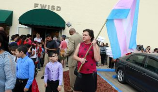 In this photo taken Tuesday, May 10, 2016, a young boy leaving a special recognition ceremony at the Fort Worth School board meeting looks at Karli Rampage, right, of Irving, Texas, who came in support of her transgender community at the Fort Worth ISD Board of Education complex, in Fort Worth, Texas. Fort Worth Superintendent Kent Scribner announced rules last month allowing transgender students access to single-stall restrooms. (Tom Fox/The Dallas Morning News via AP) **FILE**