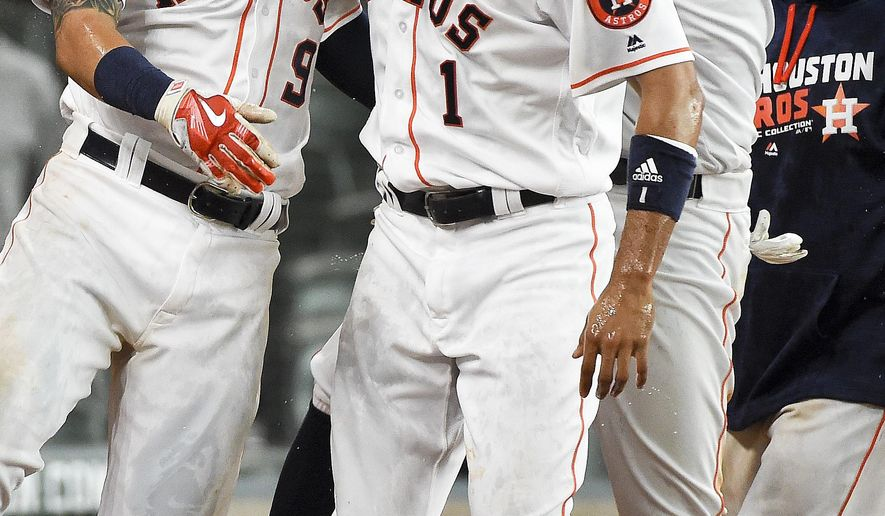 Houston Astros' Marwin Gonzalez (9) celebrates his game-winning two-run home run with Carlos Correa (1) and George Springer, right, in the 16th inning of a baseball game against the Cleveland Indians, Wednesday, May 11, 2016, in Houston. Houston won 5-3. (AP Photo/Eric Christian Smith)