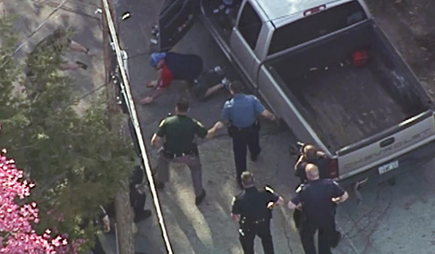 This aerial image made from a helicopter video provided by WHDH shows Richard Simone kneeling and putting his hands on the ground after a high-speed police pursuit in Nashua, N.H., Wednesday, May 11, 2016. Moments later several officers rushed Simone and pummeled him. (Courtesy WHDH via AP) MANDATORY CREDIT; BOSTON OUT