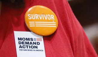 "Kari Wahnee wears a button for ""Moms Demand Action for Gun Sense in America"" during an interview in the Senate Gallery in Oklahoma City, Wednesday, May 11, 2016. Wahnee's son Bradley, a sophomore at Oklahoma City University, was caught in the crossfire during a gang-related, drive-by shooting that remains unsolved. Wahnee is a member of the Oklahoma chapter of Moms Demand Action for Gun Sense in America, one of several groups and institutions opposed to a gun bill that would allow people to carry guns in public with no training or background checks, and a separate bill pending in the Oklahoma Legislature. (AP Photo/Sue Ogrocki) ** FILE **"