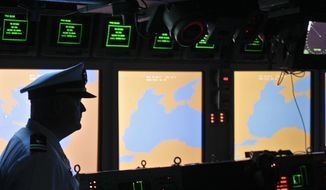 In this Tuesday, June 7, 2011, file photo, a U.S. Navy officer, name not available, stands on the weapons control deck of the USS Monterey as screens display the Black Sea region, in the Black Sea port of Constanta, Romania. A U.S. missile defense system aimed at protecting Europe from ballistic missile threats is moving into higher gear this week, with a site in the village of Deveselu, Romania, becoming operational on Thursday, May 12, 2016, and officials breaking ground at a separate site in Poland a day later. (AP Photo/Vadim Ghirda, File)