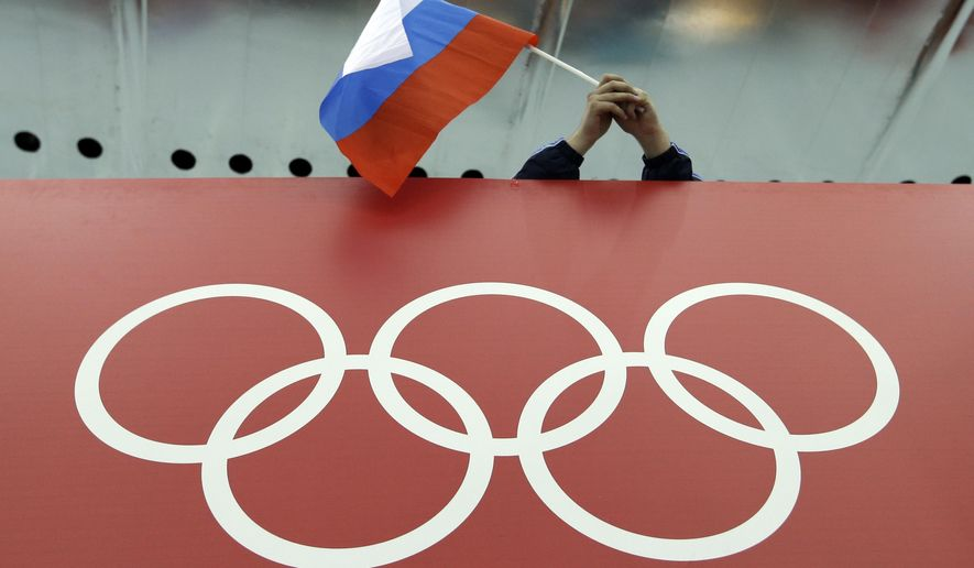 "FILE - In this Feb. 18, 2014 file photo, a Russian skating fan holds the country's national flag over the Olympic rings before the start of the men's 10,000-meter speedskating race at Adler Arena Skating Center during the 2014 Winter Olympics in Sochi, Russia. A whistleblower who uncovered Russia's doping scourge says most of the changes in the country's track and anti-doping programs are, in his words, ""just fake,"" and not extensive enough to allow the team into this summer's Olympics. Vitaly Stepanov, who along with his wife, Yulia, blew the lid off systemic doping in Russia, tells The Associated Press that about 80 percent of coaches in Russian track used doping to prepare athletes for London's Olympics. (AP Photo/David J. Phillip, File)"