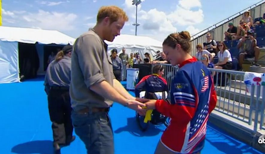 U.S. Army Sgt. Elizabeth Marks gives her gold metal from the Invictus Games to Prince Harry. She asked that the metal be donated to the hospital that saved her life. (ABC News screenshot)