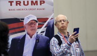 Glen Hettinger makes a photo of himself with a photo of Donald Trump in the exhibition hall during the Texas Republican Convention Thursday, May 12, 2016, in Dallas. (AP Photo/LM Otero)
