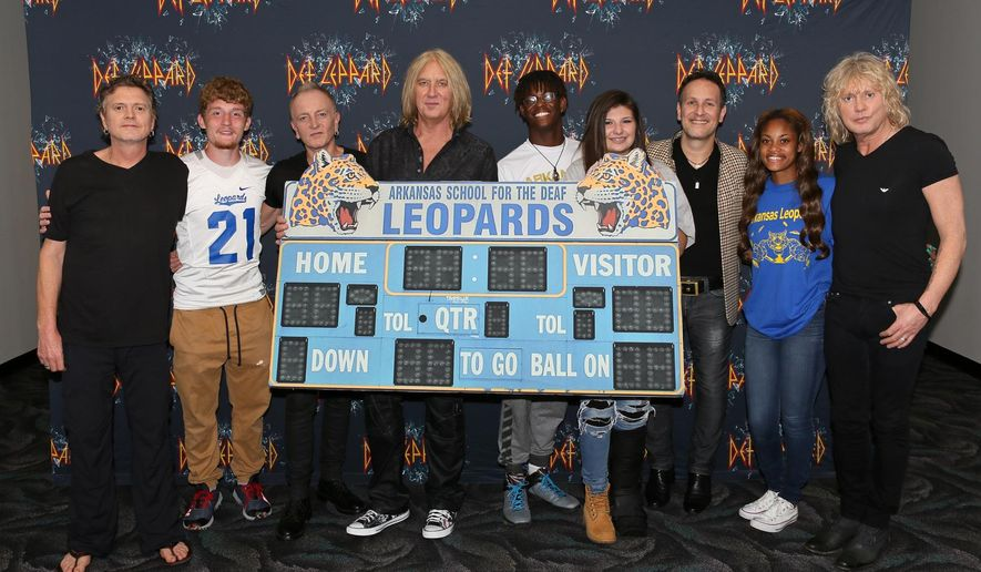 "CORRECTS DATE TO MAY 11 - In this May 11, 2016 photo provided by Nelson Chenault, from left, Def Leppard drummer Rick Allen, student Stephen Cathcart, guitarist Phil Collen, lead singer Joe Elliott, student Henry James, student Alex Gossett, guitarist Vivian Campbell, student Jewel Brandon and bassist Rick Savage pose with a replica of the scoreboard from the Arkansas School for the Deaf, before a concert in North Little Rock, Ark. The British rockers behind a string of hits in the 1980s and '90s including ""Pour Some Sugar on Me"" and ""Photograph"" met with students whose team's name is the Leopards. (Nelson Chenault via AP)"