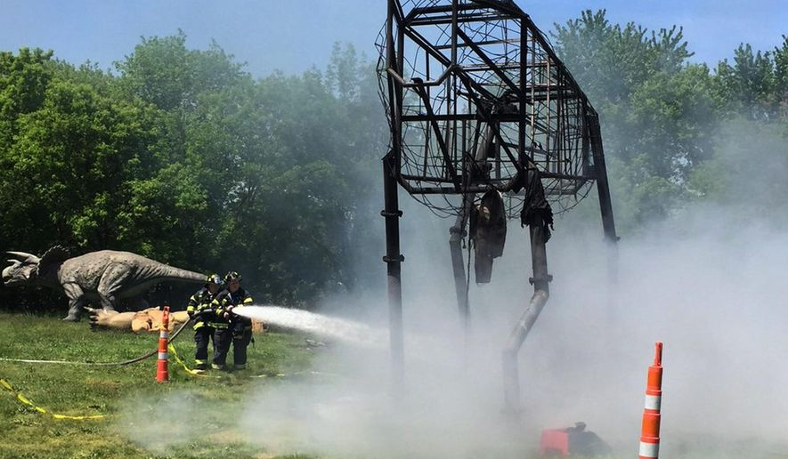 This photo provided by the Leonia, N.J., Police Department shows a fire that destroyed a 90-foot animatronic dinosaur at Overpeck County Park in Leonia, N.J., Thursday, May 12, 2016. The fire has destroyed the animatronic dinosaur that was set to be part of an exhibit at the theme park. (Leonia Police Department via AP)