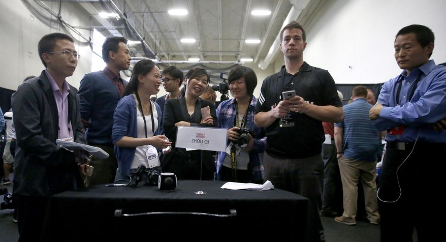 Reporters wait to interview Zhou Qi, from China, during the NBA basketball draft combine Thursday, May 12, 2016, in Chicago. (AP Photo/Charles Rex Arbogast)