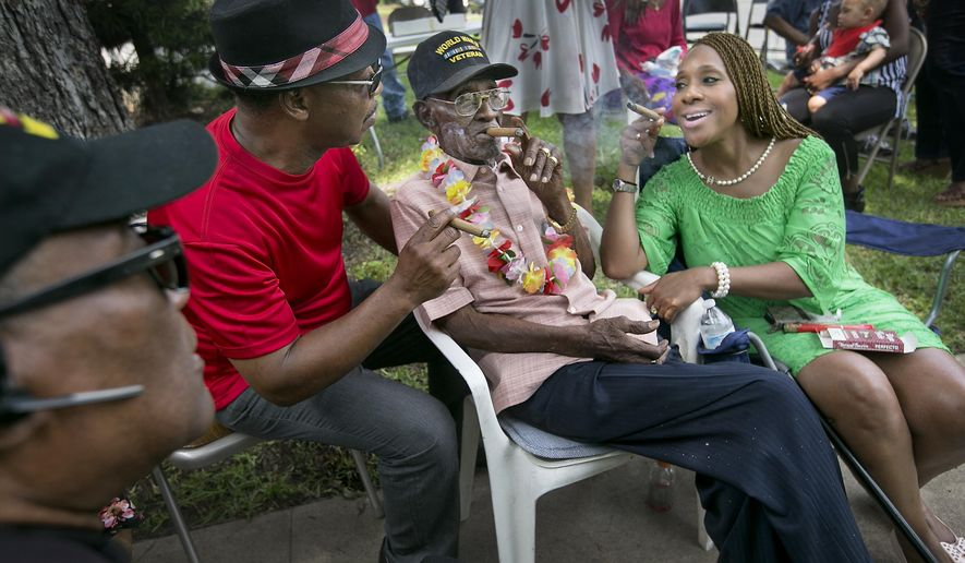 World War II veteran, Richard Overton celebrates his 110th birthday on Wednesday, May 11, 2016, with friends and family at his home in Austin, Texas.  He smokes a cigar with caregiver Martin Wilford, left,  and good friend  Donna Shorts. Pastor Carl Jarman, far left, sits nearby. Overton, who was born in Bastrop County in 1906, served in the Pacific Theater from 1942 to 1945 as part of the all-black 1887th Engineer Aviation Battalion. After the war, he returned to Austin, and he has lived in the same home ever since. (Laura Skelding\Austin American Statesman via AP)
