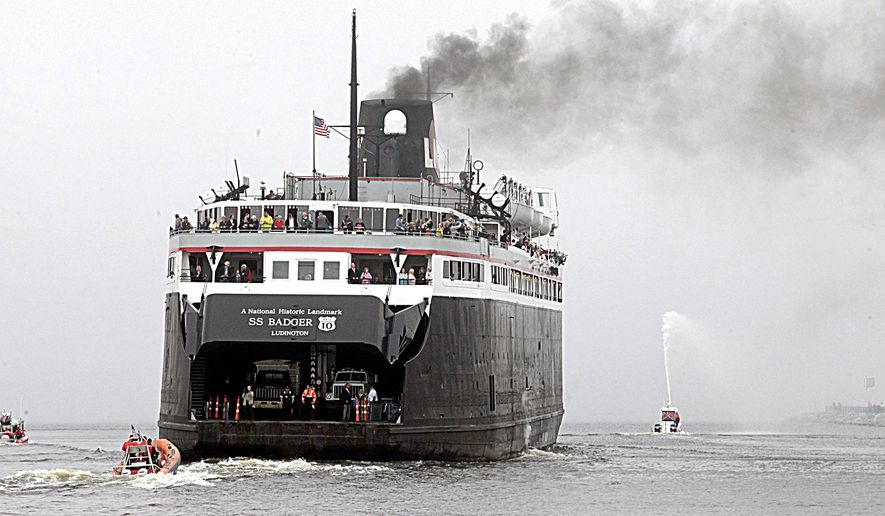 "The SS Badger ferry, with the words ""A National Historic Landmark"" on her stern apron, makes its way out of the Ludington channel under escort, Thursday, May 12, 2016, in Ludington, Mich., heading to Manitowoc, Wis. The designation, which had been sought for years, was announced last January. The 410-foot vessel, launched into service on Lake Michigan between Wisconsin and Michigan in 1952, can carry 600 passengers and 180 vehicles. (Jeff Kiessel/Ludington Daily News via AP)  MANDATORY CREDIT (REV-SHARE)"