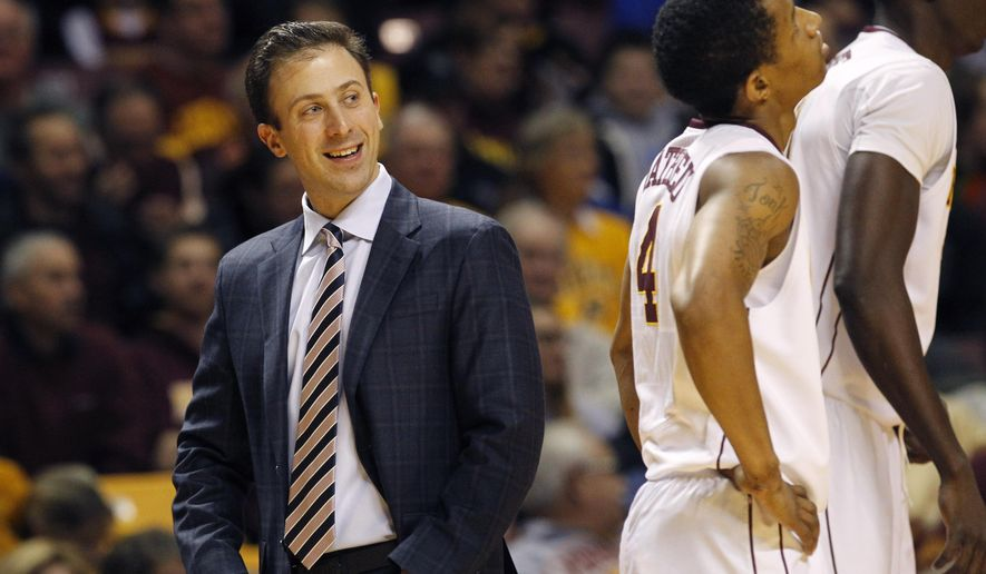 FILE - In this Friday, Dec. 19, 2014 file photo, Minnesota head coach Richard Pitino, left, smiles at his players during the first half of an NCAA college basketball game against Seattle in Minneapolis. With concern expressed by the university president and a new athletic director now in place at Minnesota, head coach Richard Pitino is under pressure to restore the Gophers men's basketball program to respectability off and on the court. (AP Photo/Ann Heisenfelt, File)