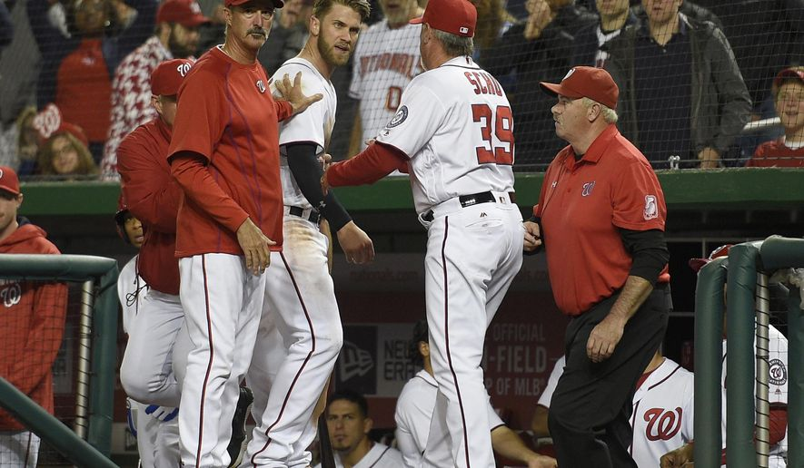 FILE - In this May 9, 2016 file photo, Washington Nationals' Bryce Harper, center, is restrained by pitching coach Mike Maddux, left, and hitting coach Rick Schu (39) after Harper was ejected in the dugout during the ninth inning of an interleague baseball game against the Detroit Tigers, in Washington. If things were quiet around the club on Thursday, May 12, 2016, it's only because it was a day off. The way things have been going lately, there's no telling what will happen when the Nationals host the Miami Marlins for a four-game series starting Friday, May 13, 2016. (AP Photo/Nick Wass, File)
