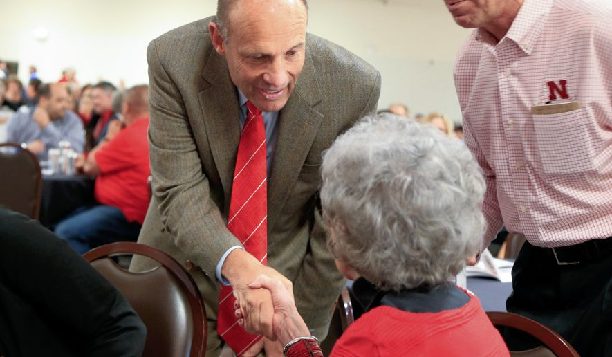 In this May 11, 2016 photo, Nebraska NCAA college football head coach Mike Riley shakes the hand of a fan at the exhibition hall of the Platte County Agricultural Society in Columbus, Neb. In the best of times Nebraska coaches made their way around the state to press the flesh. But with a conference championship drought dating to 1999, a 6-7 record in Riley's first season and an NCAA record sellout streak to protect, fan outreach would seem critically important now. (AP Photo/Nati Harnik)