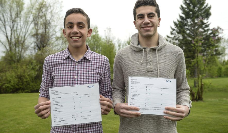Hamza Baccouche, left, and his brother Basil, pose for a photo with their ACT scores, Tuesday, May 10, 2016, in Ann Arbor, Mich. Basil and Hamza Baccouche, who go to Ann Arbor's Pioneer High School, have each gotten a 36 composite score on the exam. Basil Baccouche, who is a senior, got a perfect score first, followed by his brother Hamza, who is a junior. (Junfu Han/The Ann Arbor News via AP)