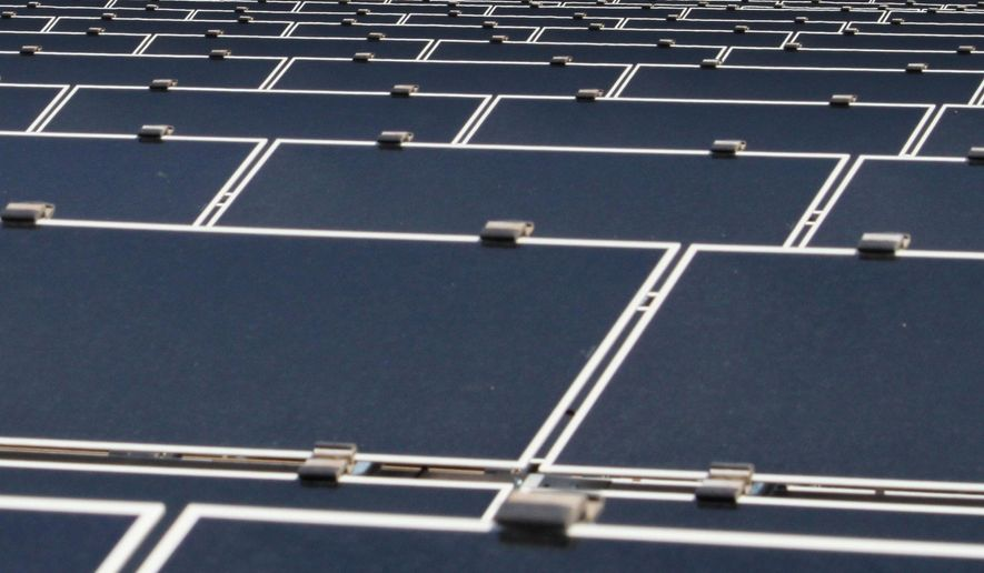 FILE - This April 20, 2011, file photo shows dozens of rows of solar panels that make up Public Service Co. of New Mexico's 2-megawatt photovoltaic array in front of transmission lines near the utility's natural gas-fired generating station in Albuquerque, N.M. The holding company for New Mexico's largest electric provider has opted to host its annual shareholders' meeting in Texas this year, and on the ballot is a proposal that would require Public Service Co. of New Mexico to adopt goals for reducing greenhouse gas emissions. (AP Photo/Susan Montoya Bryan)