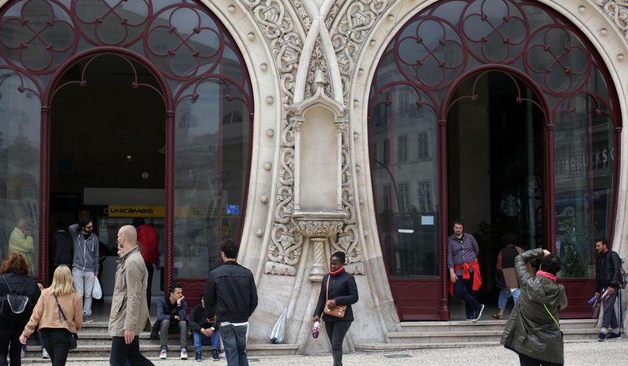 A woman takes pictures by the front doors of Lisbon's Rossio train station, a national monument, Thursday, May 12 2016. A statue of 16th-century King Sebastian, around 1-meter (3-feet) tall, stood in the now empty head-high niche between the doors. Portuguese officials said Thursday they are trying to put a value on the 19th-century statue broken when a man climbed up it late at night to take a photo, possibly a selfie. (AP Photo/Armando Franca)