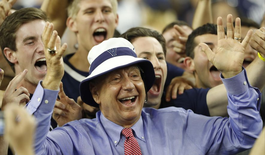 FILE - In this April 4, 2016, file photo, sportscaster Dick Vitale poses with Villanova fans before the NCAA Final Four tournament college basketball championship game between Villanova and North Carolina, in Houston. If you're a college basketball fan imagine how much fun it would be to exchange text messages with Dick Vitale. Instead of the texts being full of catchphrases, predictions and analysis, they are full of sobering stories. Stories about pediatric cancer. It is his passion and he wants to make sure he touches every vein that can bring more money for research. (AP Photo/Eric Gay, File)