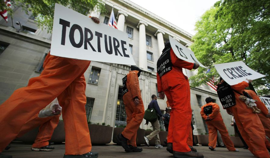 Hooded protestors dressed to resemble prisoners at Guantanamo Bay march past the Justice Department in Washington on April 30, 2009. (Associated Press) **FILE**