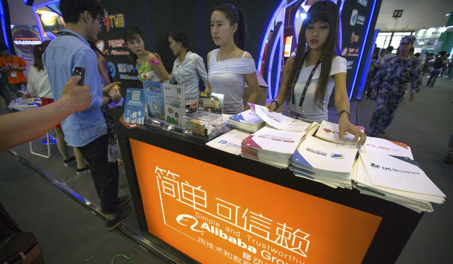 In this April 29, 2015, file photo, staff members hand out brochures to visitors at the Alibaba booth at the Global Mobile Internet Conference in Beijing. (AP Photo/Mark Schiefelbein) ** FILE **
