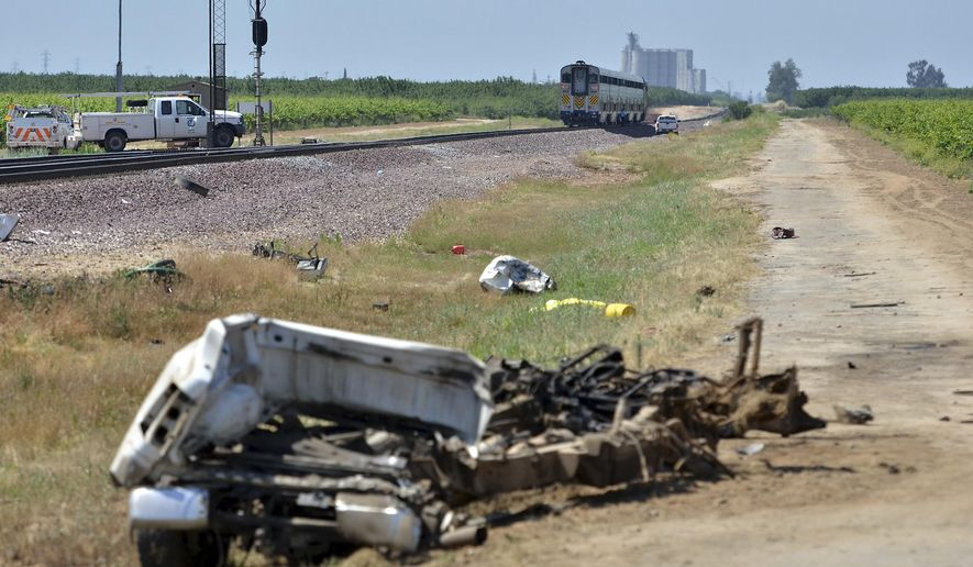 An Amtrak train sits on the tracks after it hit a pickup truck that was attempting to cross the tracks near a canal Friday, May 13, 2016, in Madera, Calif. A few men in a pickup truck died when the driver pulled in front of a speeding Amtrak passenger train, splitting the truck in two but causing no serious injuries to the train's passengers, authorities said. (Silvia Flores/The Fresno Bee via AP) MANDATORY CREDIT