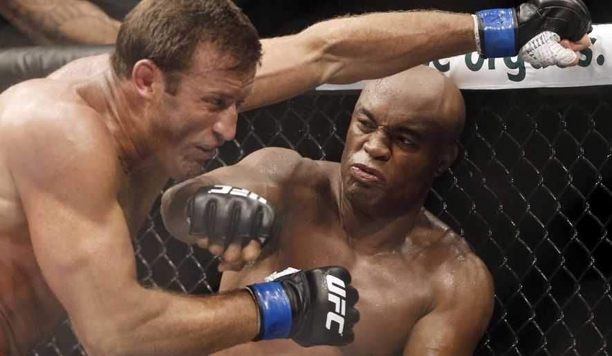 FILE - In this Oct. 14, 2012, file photo, Brazil's Anderson Silva, right, throws a punch at Stephan Bonnar, of the United States, during their light heavyweight mixed martial arts bout at UFC 153 in Rio de Janeiro, Brazil. Former UFC middleweight champion Anderson Silva has withdrawn from his scheduled fight against Uriah Hall of Jamaica on Saturday, May 14, 2016, in the city of Curitiba in southern Brazil. Organizers of the event did not provide details for the 41-year-old's decision, and said Hall will not face a different opponent. (AP Photo/Felipe Dana, File)