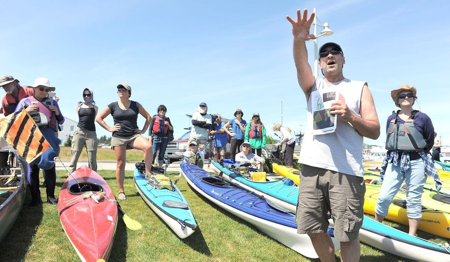 Kayakers listen to a talk on eelgrass and the care that should be taken in not disturbing it near Seafarer's Memorial Park in Anacortes, Wash., Friday, May 13, 2016. Hundreds of people in kayaks and on foot gathered at the site of two oil refineries in Washington state to call for action on climate change and a fair transition away from fossil fuels. (Scott Terrell/Skagit Valley Herald via AP) MANDATORY CREDIT