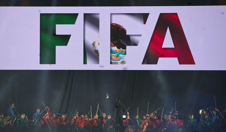 A youth orchestra plays behind a screen marked with FIFA in the colors of the Mexican flag, during the opening ceremony of the 66th FIFA Congress, held in Mexico City, Thursday, May 12, 2016. (AP Photo/Rebecca Blackwell)