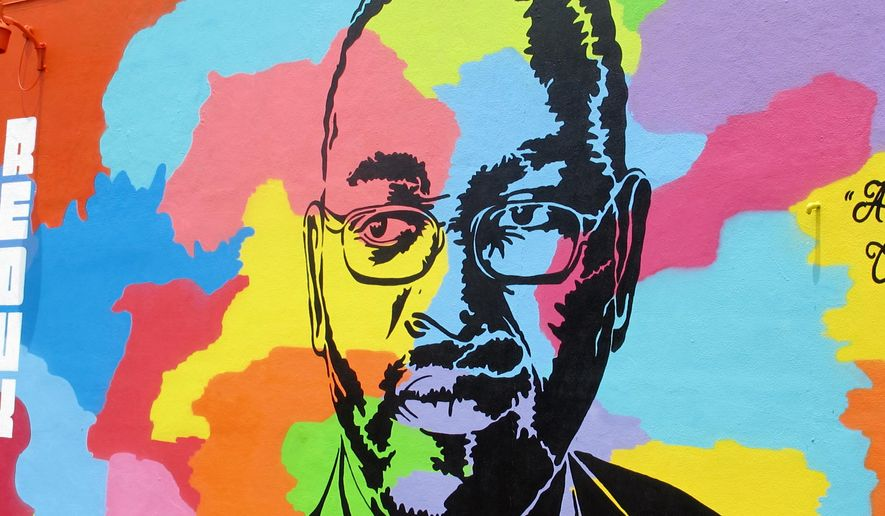 An image of the Rev. Clementa Pinckney, one of the victims of the June 2015 shootings at Emanuel AME Church in Charleston, S.C., is seen on a mural on a building in Charleston a few blocks from the church on Friday, May 13, 2016. The mural was created by artist Tripp Derrick Barnes to honor the nine shooting victims as the first anniversary of the slayings approaches. (AP Photo/Bruce Smith)