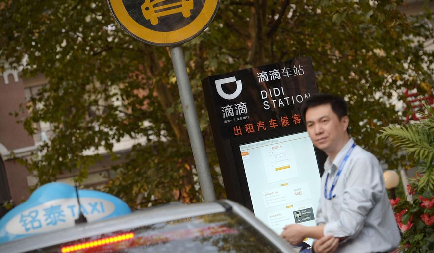 In this Thursday, Oct. 15, 2015 photo, a taxi driver waits at a newly-installed Didi Station, a road-side stop for taxis booked by the Chinese car-hailing app Didi Kuaidi, which has since changed its name to Didi Chuxing, in Shanghai. Didi Chuxing announced Friday, May 13, 2016, that Apple has invested $1 billion in the company and will become a strategic investor alongside Chinese e-commerce giant Alibaba Group and Tencent Holdings Ltd., an online games and entertainment service. (Chinatopix via AP) CHINA OUT