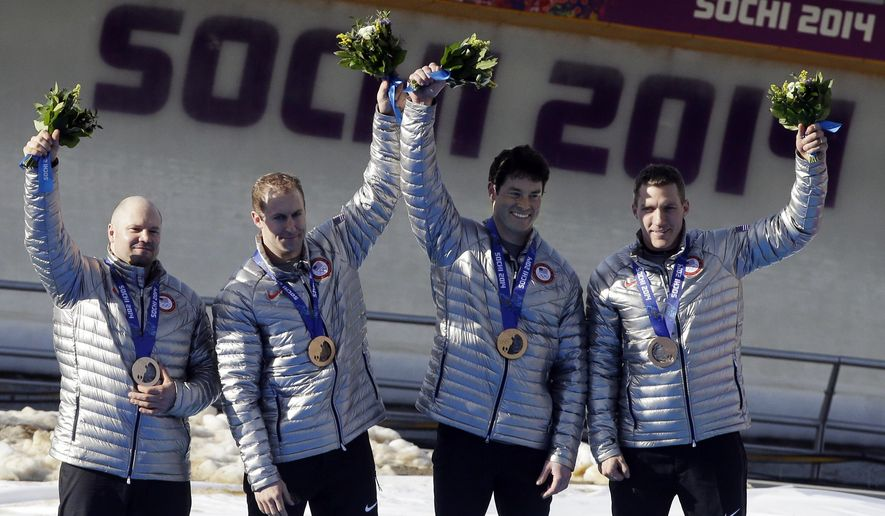 FILE - In this Feb. 23, 2014, file photo, members of the USA-1 team Steven Holcomb, left, Curtis Tomasevicz, Steven Langton and Christopher Fogt, celebrate after they won bronze in the men's four-man bobsled at the Winter Olympics in Krasnaya Polyana, Russia. Holcomb won two bronze medals at the Sochi Olympics that could be upgraded to silver if doping allegations against the Russians are proven. (AP Photo/Dita Alangkara, File)