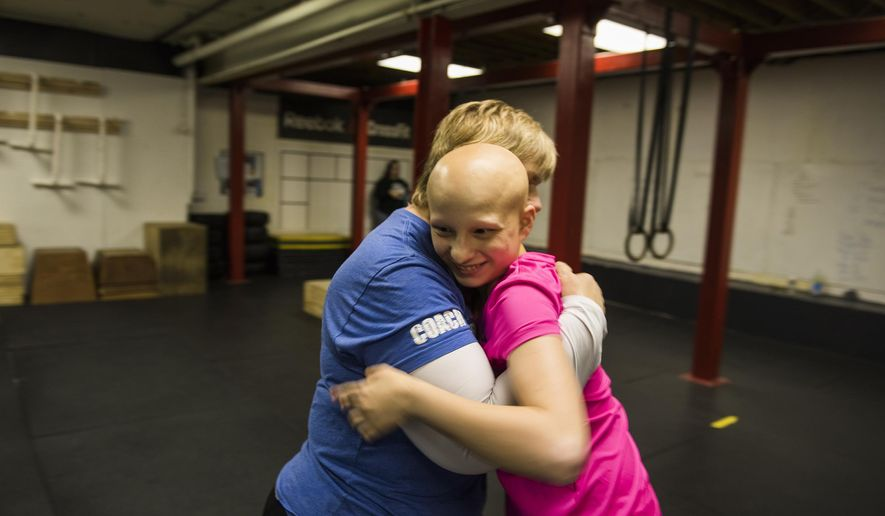 "ADVANCE FOR SATURDAYMAY 14 AND THEREAFTER - In a Feb. 17, 2016 photo, Katie Krotz, 17, gives a hug to her Crossfit instructor, Sheron Smith, while attending a session of Smith's ""Special Warriors"" Crossfit program at Hanover Crossfit in Hanover, Pa. The program is designed for children with autism or other learning disabilities by keeping them active. Smith has also developed a close bond with Krotz. (Shane Dunlap/The Evening Sun via AP) MANDATORY CREDIT"