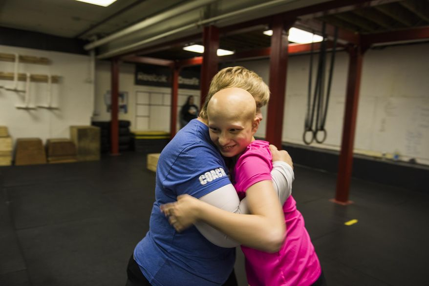 """ADVANCE FOR SATURDAYMAY 14 AND THEREAFTER - In a Feb. 17, 2016 photo, Katie Krotz, 17, gives a hug to her Crossfit instructor, Sheron Smith, while attending a session of Smith's """"Special Warriors"""" Crossfit program at Hanover Crossfit in Hanover, Pa. The program is designed for children with autism or other learning disabilities by keeping them active. Smith has also developed a close bond with Krotz. (Shane Dunlap/The Evening Sun via AP) MANDATORY CREDIT"""