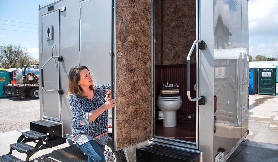 In this April 22, 2016 photo, Michelle Van Wynen, of Gulliford Services/Illinois Portable Toilets, opens the door to a 12-foot luxury restroom trailer at the portable toilet supplier in Urbana, Ill. The unit, that comes with four private, self-contained bathrooms, is in so much demand as a rental for weddings, the company is looking at springing for a second. (John Dixon/The News-Gazette via AP) MANDATORY CREDIT MANDATORY CREDIT