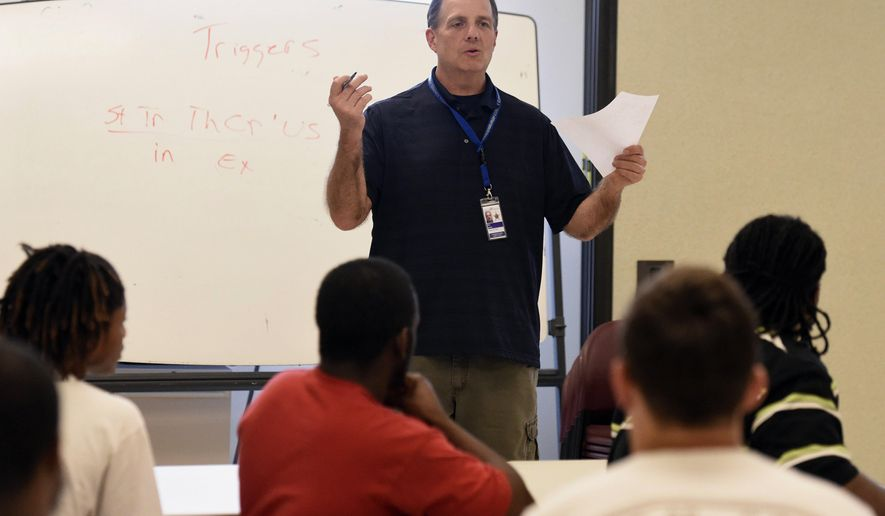 "In this April 27, 2016 photo, therapy work release counselor James Aiken leads a class about substance abuse and ""triggers"" at the Vanderburgh County Sheriff Administration, Detention and Corrections facility in Evansville, Ind. Vanderburgh County courts have taken over responsibility for operating community corrections, transforming it into a Therapeutic Work Release program emphasizing rehabilitation of inmates and not just incarceration. (Jason Clark/Evansville Courier & Press via AP) MANDATORY CREDIT"