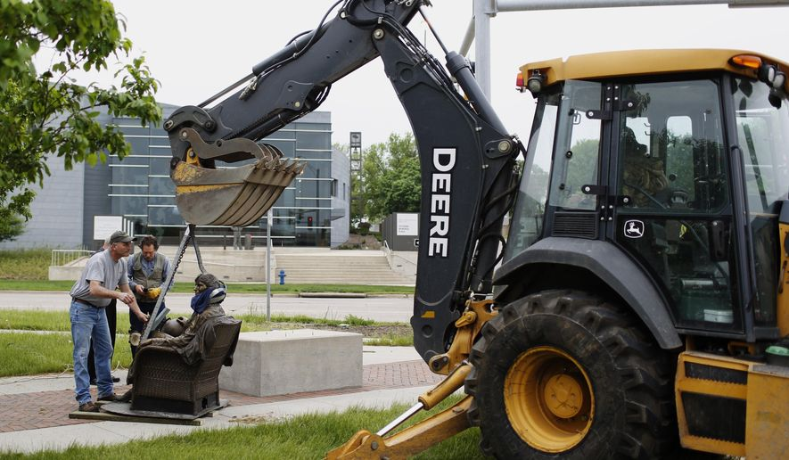 In this Wednesday, May 11, 2016 photo, Larry Vogel, left, and Rick Wagner, with Waterloo Leisure Services, use a backhoe to install Chris Bennett's bronze statue of Lou Henry Hoover in Waterloo, Iowa. (Matthew Putney/The Courier via AP) MANDATORY CREDIT