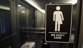 In this photo taken Thursday, May 12, 2016, signage is seen outside a restroom at 21c Museum Hotel in Durham, N.C.  (AP Photo/Gerry Broome)