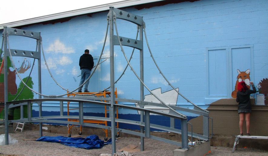 """In this April 30, 2016 photo, Traverse City artist Peter Abrami, center, and Interlochen Arts Academy visual arts student Bella Rios of West Hartford, Conn., paint portions of a mural on the side of the Great Lakes Children's Museum building in Traverse City, Mich. The museum now has its own """"Mini-Mac,"""" a smaller version of the Mackinac Bridge connecting Michigan's Upper and Lower peninsulas. (Marta Hepler Drahos/Traverse City Record-Eagle via AP) MANDATORY CREDIT"""