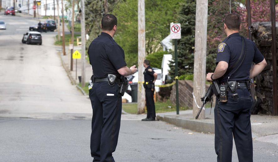 Police stand guard as the search continues for a suspect who shot two police officers overnight Friday, May 13, 2016, in Manchester, N.H.  Authorities say the officers were shot early in the morning and are recovering at hospitals. (AP Photo/Jim Cole)
