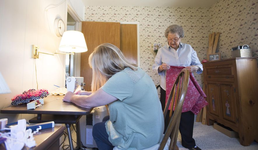 In this photo taken Wednesday, May 4, 2016, Kris Evertsen, of Clinton, left, threads the needle of her mom's sewing machine at her mom's house in Washington Terrace, Utah. Since Helen Peterson, 94,  started making dresses to donate to girls in Africa in January she has made over 80 dresses. Kris, Helen's youngest daughter, spends most days with her and helps with things such as preparing food and running errands. (Briana Scroggins/Standard-Examiner via AP)