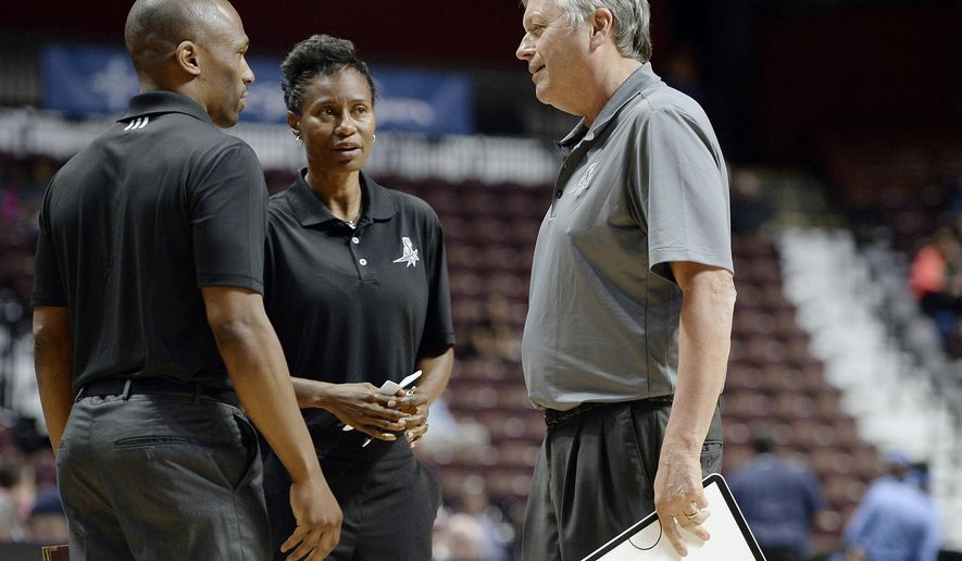 In this May 4, 2016 photo, San Antonio Stars coach Dan Hughes talks with assistant coaches James Wade, left, and Vickie Johnson, center, during the first half of the team's WNBA basketball exhibition game against the Atlanta Dream in Uncasville, Conn. The veteran coach announced last month that this will be his final year on the bench. (AP Photo/Jessica Hill)