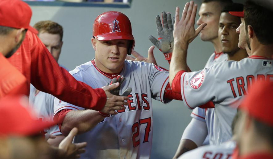 Los Angeles Angels' Mike Trout, center, is greeted in the dugout after he scored on a single by Daniel Nava during the fourth inning of a baseball game against the Seattle Mariners, Friday, May 13, 2016, in Seattle. (AP Photo/Ted S. Warren)