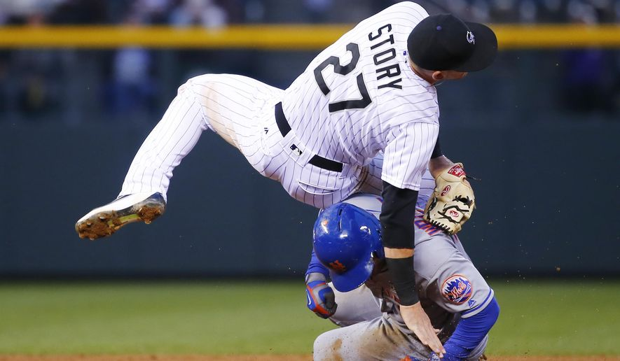New York Mets' David Wright, bottom, is forced out at second as Colorado Rockies shortstop Trevor Story falls after throwing to first to complete the double play on Michael Conforto during the fifth inning of a baseball game Saturday, May 14, 2016, in Denver. (AP Photo/Jack Dempsey)