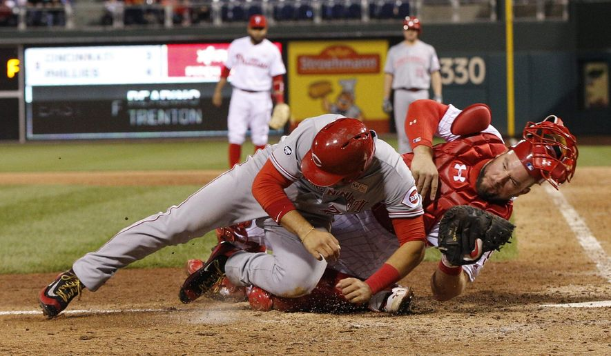 Philadelphia Phillies catcher Cameron Rupp, right, tags out Cincinnati Reds' Eugenio Suarez, left, on the double play to end the ninth inning of a baseball game, Saturday, May 14, 2016, in Philadelphia. The Phillies won 4-3. (AP Photo/Chris Szagola)
