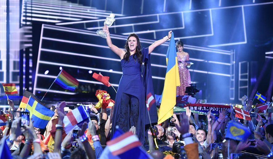 Ukraine's Jamala celebrates with the trophy after winning the Eurovision Song Contest final with the song '1944' in Stockholm, Sweden, Sunday, May 15, 2016. (AP Photo/Martin Meissner)