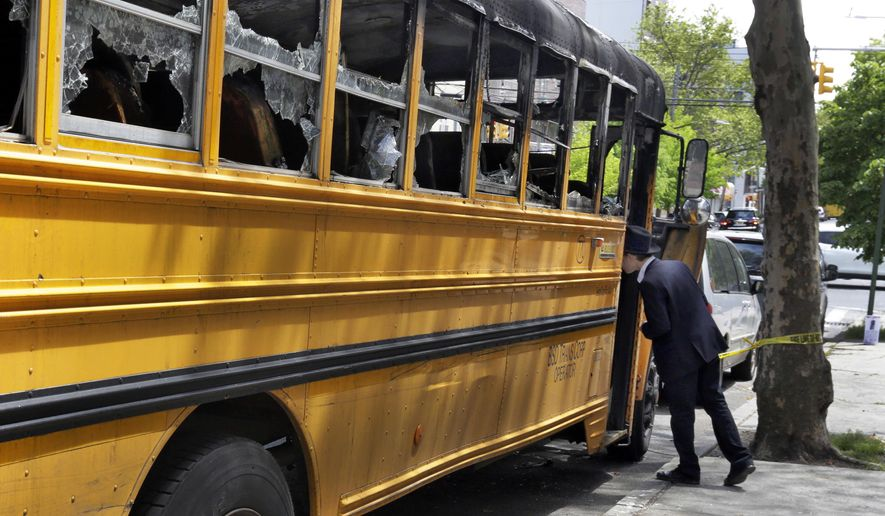 An Orthodox Jewish boy peeks into the school bus that was burned Sunday May 8, 2016, in the Crown Heights section of the Brooklyn borough of New York, Wednesday May 11, 2016. When a group of young, black children set fire to a school bus outside a Jewish school this week, it evoked bad memories of a violent riot in the same Brooklyn neighborhood 25 years ago. Relations between blacks and Jews in Crown Heights have been peaceful for many years, but some community leaders say tensions remain. (AP Photo/Richard Drew)