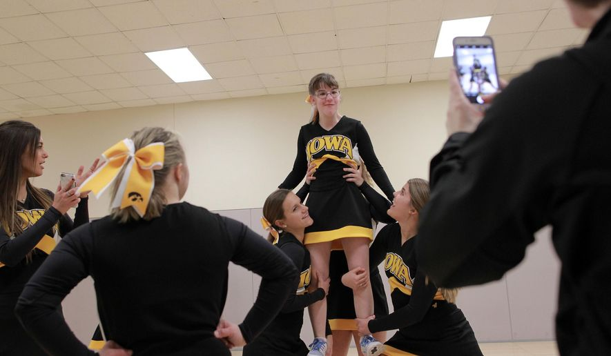 "ADVANCE FOR THE WEEKEND OF MAY 14-15 AND THEREAFTER - In a Thursday, March 3, 2016 photo, Ali Brownsberger poses for a picture during practice with the Hawkeye Sparkles at the UI Field House in Des Moines, Iowa. The Sparkle Effect, a nonprofit founded in 2008 by 15-year-old Iowa resident Sarah Cronk, helps high schools and universities start inclusive ""Sparkle"" squads, cheer or dance teams that combine typically developing students and students with disabilities. (David Scrivner/Iowa City Press-Citizen via AP)  NO SALES; MANDATORY CREDIT"