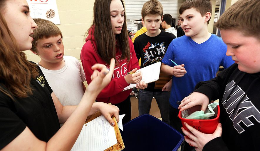 ADVANCE FOR USE SATURDAY, MAY 14 - In this photo taken April 29, 2016, students inspect buckets of food scraps from the cafeteria that will be used for composting at Bettendorf Middle School in Bettendorf, Iowa. Throughout the past six weeks, teach Nikki Armstrong has motivated her students to burst their Bettendorf bubbles and study water conservation, an issue several of them didn't know existed before this year. (Jeff Cook/Quad City Times via AP) MANDATORY CREDIT