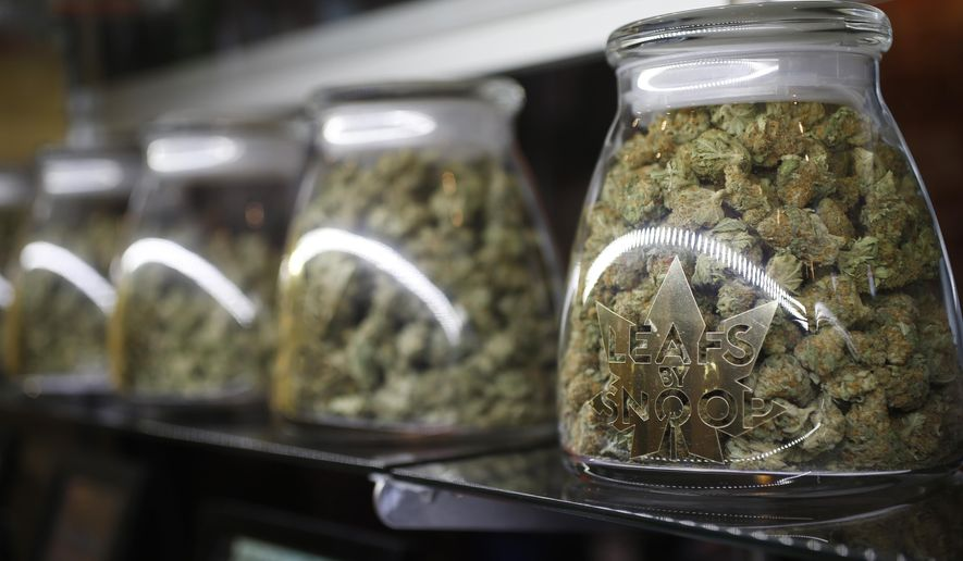 In this Friday, Dec.18, 2015, file photograph, the logo is shown on the front of jars of marijuana buds marketed by rapper Snopp Dogg in one of the LivWell marijuana chain's outlets south of downtown Denver. (AP Photo/David Zalubowski, file)