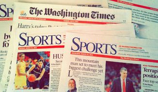 A stack of copies of The Washington Times are spread out across a desk. The sports staff of the newspaper was recently recognized for excellence in the annual Associated Press Sports Editors writing awards. (Courtesy photo)